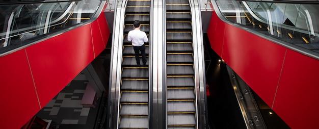 Modernas escaleras mecánicas de lujo en el auditorio con hombre de negocios