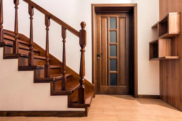 Modernas escaleras y puertas de madera de roble marrón en casa renovada