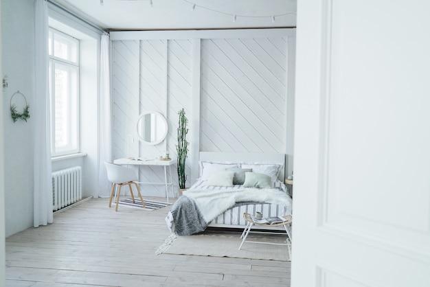 Moderno y acogedor interior escandinavo, mesa blanca y espejo en la habitación.