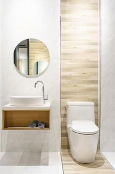 Moderno y amplio baño con azulejos brillantes con inodoro y lavabo.