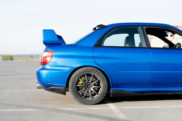 Un moderno coche azul deportivo de carrera rápida en la pista el día de práctica de verano