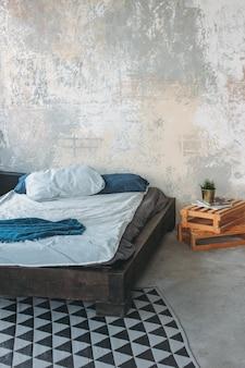 Moderno interior de loft ecológico en dormitorio, piso de concreto, cama, minimalismo.