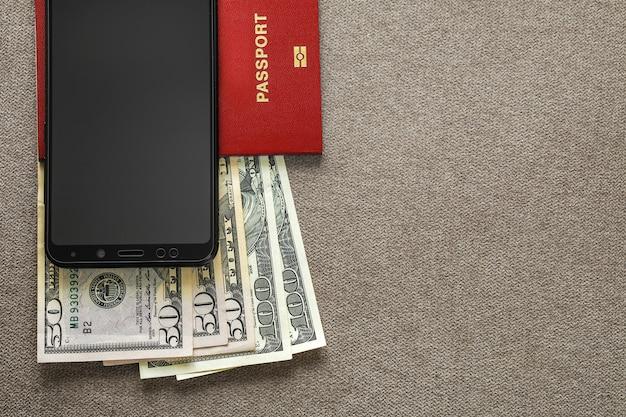 Moderno teléfono celular negro, billetes de billetes de dólares de dinero y pasaporte de viaje en el fondo del espacio de la copia. viajando ligero, cómodo concepto de viaje.