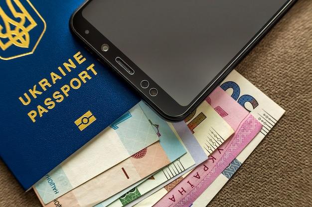Moderno teléfono celular negro, billetes de dinero hryvnia billetes