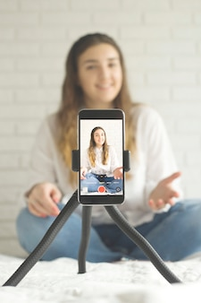 Moderno teléfono móvil disparando video con blogger femenino.
