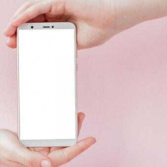 Moderno teléfono móvil en la mano de una mujer sobre fondo rosa