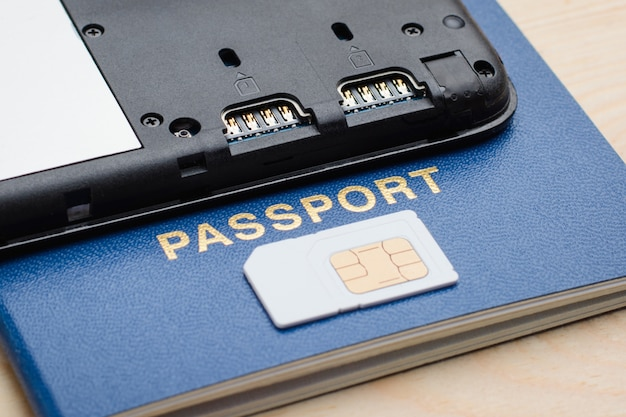 Moderno teléfono móvil en un pasaporte cerca de una tarjeta sim. tarjeta sim de registro e identificación para teléfono móvil con pasaporte