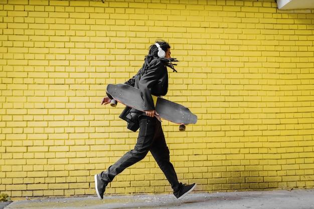 Moderno urbano joven rastas hipster hombre corriendo con su patín en sus manos y escuchando música.