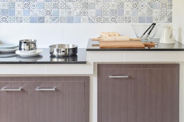 Modernos utensilios de cocina de cerámica y utensilios en la encimera de granito negro