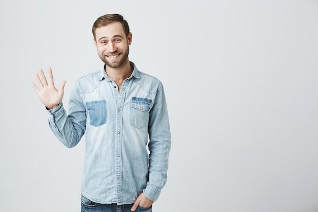 Modesta hombre barbudo lindo saluda, saludando con la mano