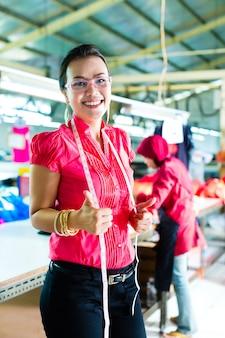 Modista asiática en una fábrica textil