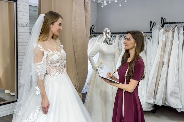 Modista con bloc de notas en salón de bodas y novia