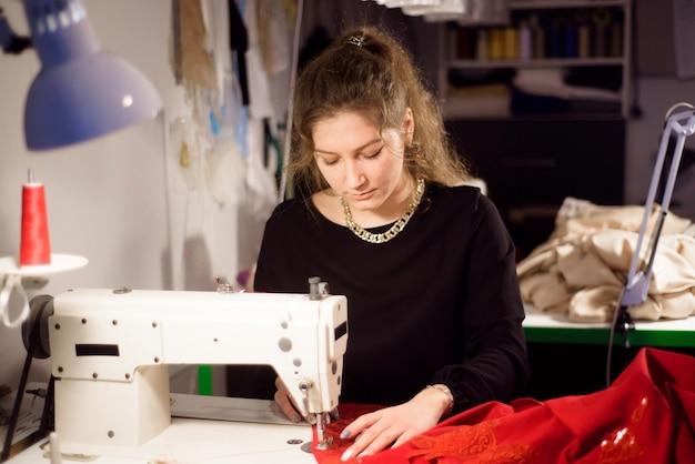 Modista trabajando en la máquina de coser. confección de una prenda a medida. hobby coser como un concepto de pequeña empresa.
