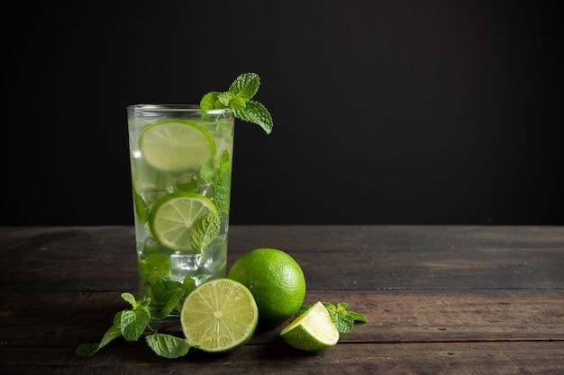 Mojito de bebida con lima, limón y menta en mesa de madera.