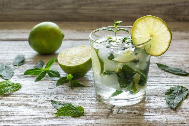 Mojito cocktail con limón y menta en vaso highball sobre un fondo blanco de madera