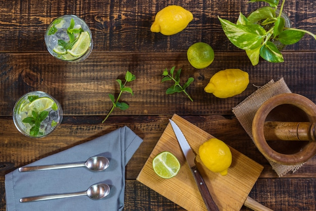 Mojito cocktail con sus ingredientes en una mesa de madera.