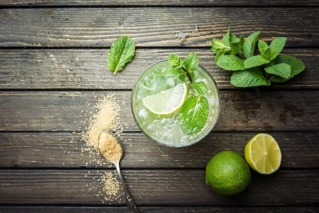 Mojito de cóctel de menta refrescante con ron y lima, bebida fría o bebida con hielo en la superficie de madera blanca, vista superior