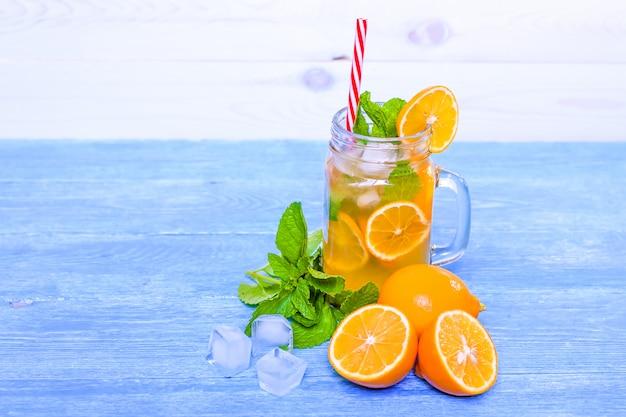 Mojito cóctel de verano con menta, jugo de limón, agua de soda y hielo en una mesa de madera blanca azul.