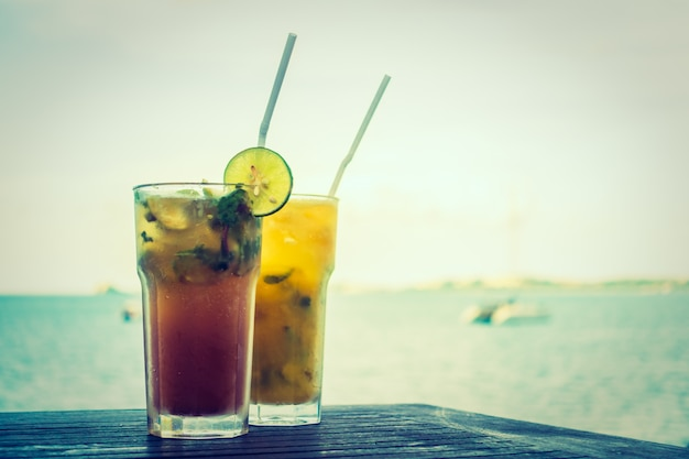 Mojito de hielo bebiendo vaso con mar tropical