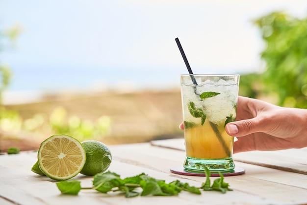 Mojito listo para beber con la playa en el fondo. concepto de bebida para el verano.
