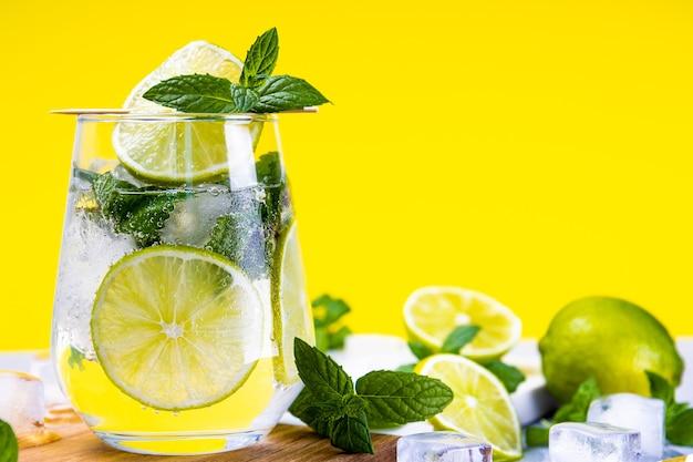 Mojito refrescante con limón y menta y hielo en un vaso sobre un fondo amarillo de verano