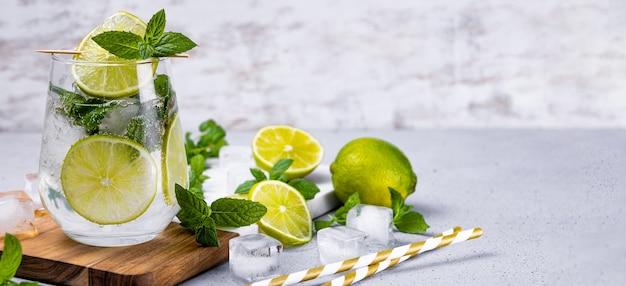 Mojito refrescante con limón y menta y hielo en un vaso sobre un fondo blanco.
