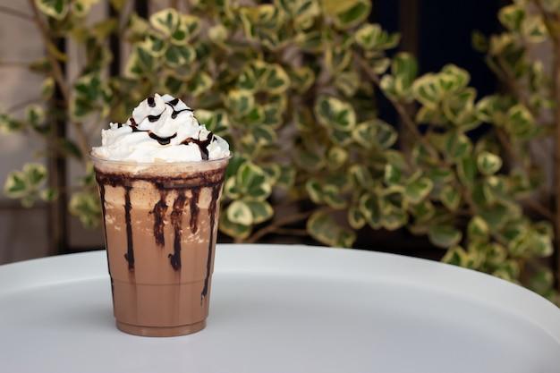 Moka frappe en vaso de plástico. servido con crema batida y salsa de chocolate. bebida de frescura. menú de bebidas favoritas con cafeína.