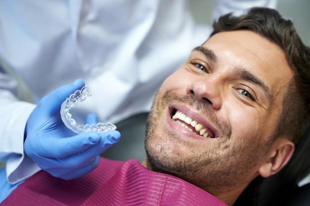 Molde de dientes de silicona para un joven en un sillón dental