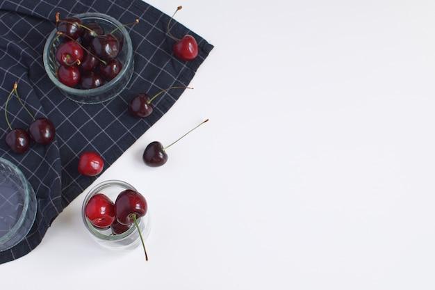 Molde para hornear y servilleta negra a cuadros cerezas maduras