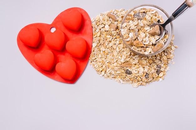 Molde de silicona y muesli en forma de corazón rojo sobre fondo gris definitivo.