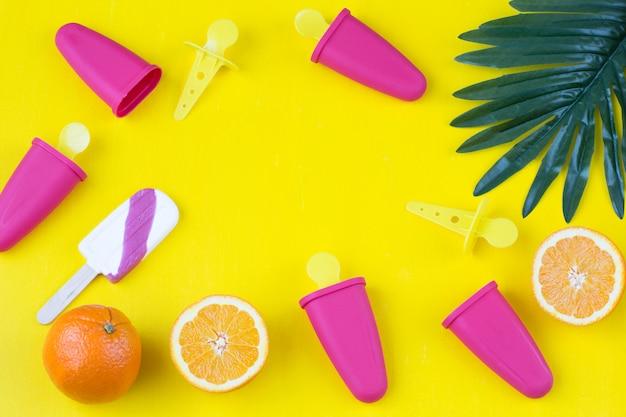 Moldes para helados, helados, naranjas y hojas de palma.