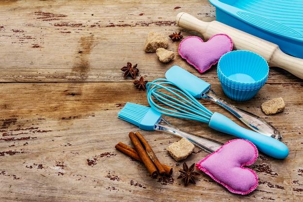 Moldes de silicona para cupcakes, especias, azúcar, batidor, espátula, rodillo y corazones de fieltro. viejas tablas de madera