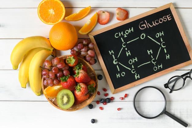 Molécula de glucosa en pizarra con frutas frescas mixtas