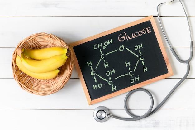 Molécula de glucosa en pizarra con plátano y estetoscopio