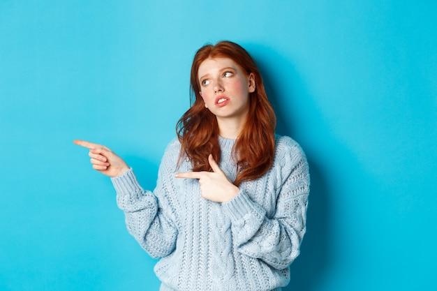 Molesta adolescente pelirroja pone los ojos en blanco, apuntando con el dedo hacia algo aburrido o cojo, de pie irritada sobre fondo azul.