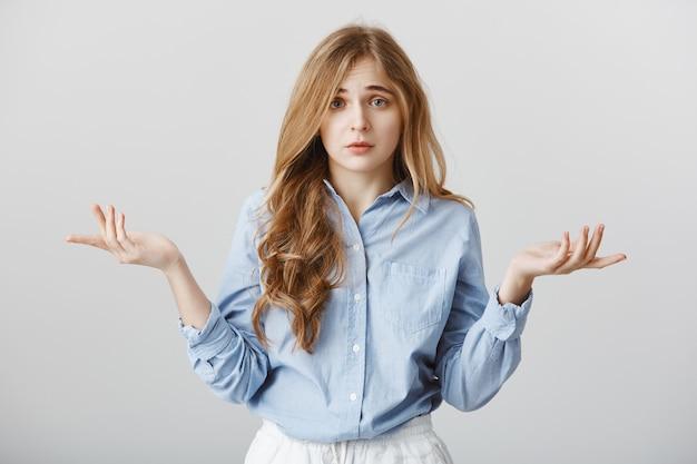 Molesto por la falta de opciones. retrato de modelo de mujer caucásica miserable sombría extendiendo las palmas y levantando las cejas, sintiendo desesperación y confusión, sin tener idea de qué hacer, de pie sobre una pared gris