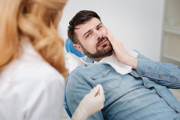 Molesto joven caballero preocupado que explica a su médico sus síntomas mientras la visita y le pide ayuda