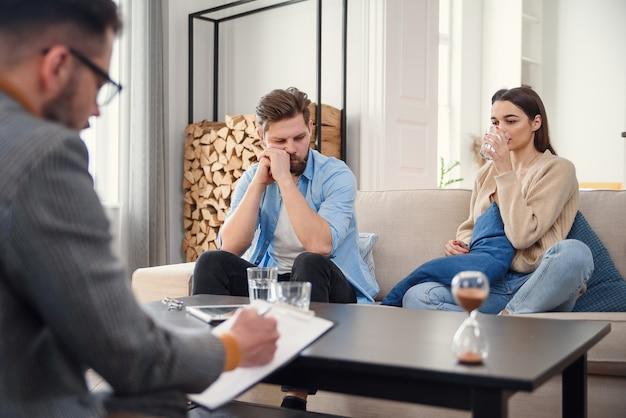 Molesto pareja caucásica de hombre y mujer conversando con psicólogo en sesión de terapia en sala de luz.