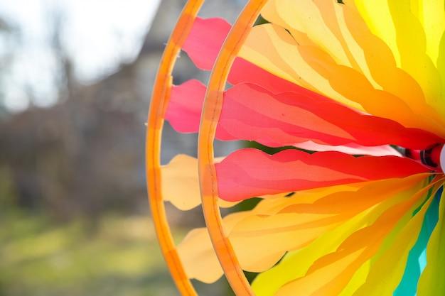 Molinete colorido que gira en el viento delante de un fondo verde natural. foco en el centro del molinete. juguete colorido. decoraciones de fiesta divertidas