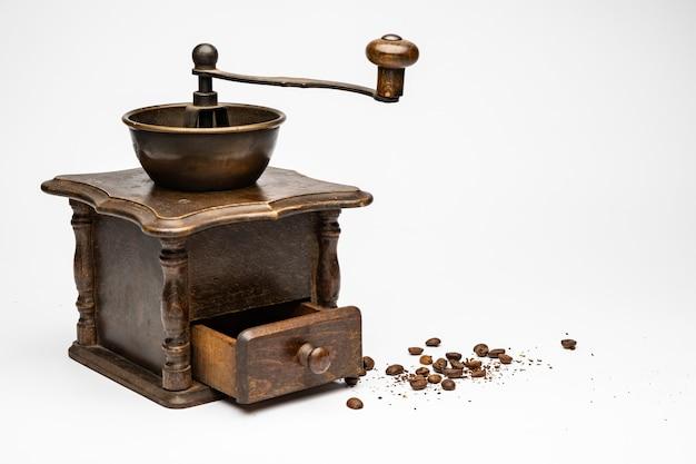 Molinillo de café antiguo con pequeños granos de café al lado y fondo blanco.