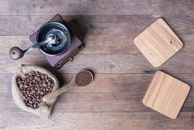 Molinillo de café, granos de café en arpillera y placa de madera en blanco sobre mesa de madera, plano con espacio de copia