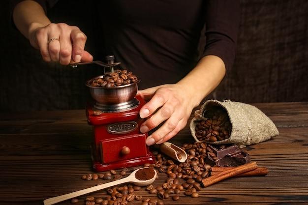Un molinillo de café y manos femeninas.