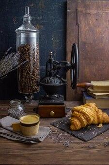 Molinillo de café vintage café y croissant sobre un fondo oscuro
