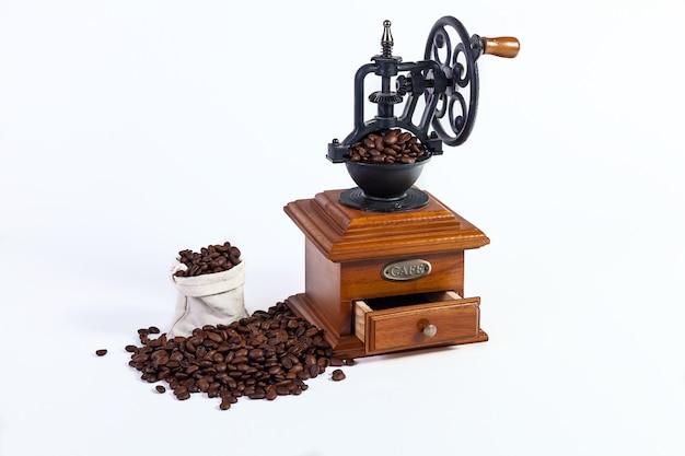 Un molinillo de mano antiguo para moler granos de café, granos de café tostados sobre un fondo blanco.