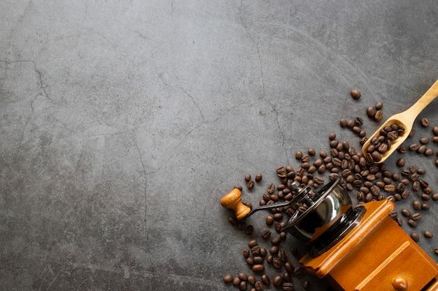 Molinillo de mano y grano de café sobre fondo de cemento antiguo