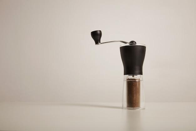 Molinillo de rebabas manual delgado moderno con café recién molido en la mesa blanca en la pared blanca