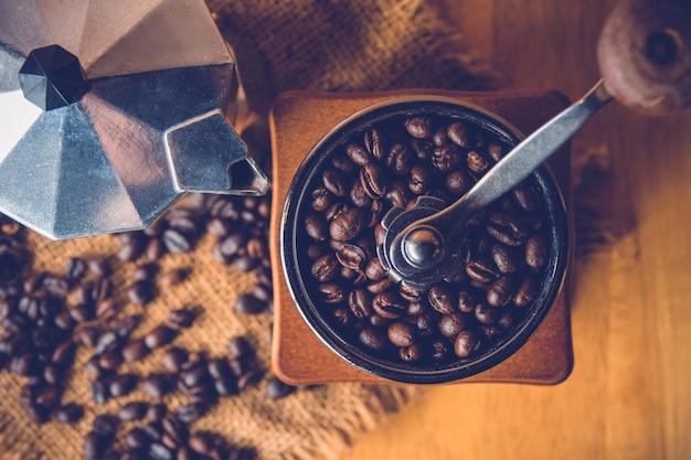 Molinillos de café antiguos con granos de café y olla moka
