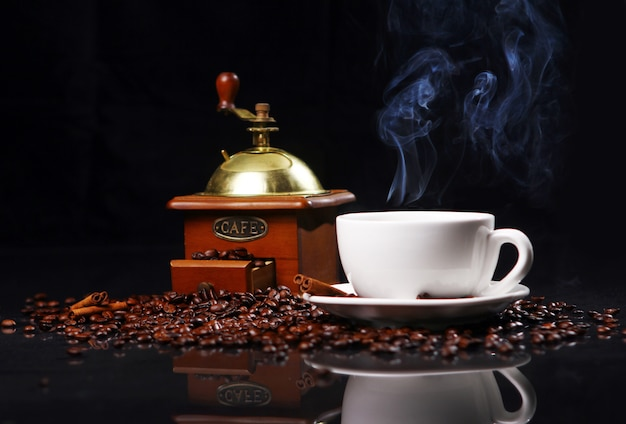 Molino de café sobre la mesa con granos de café alrededor