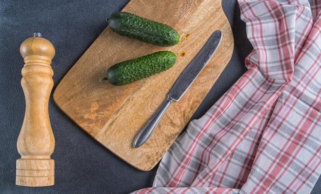 Molino de pimienta, pepinos y cuchillo de cocina en tabla de cortar