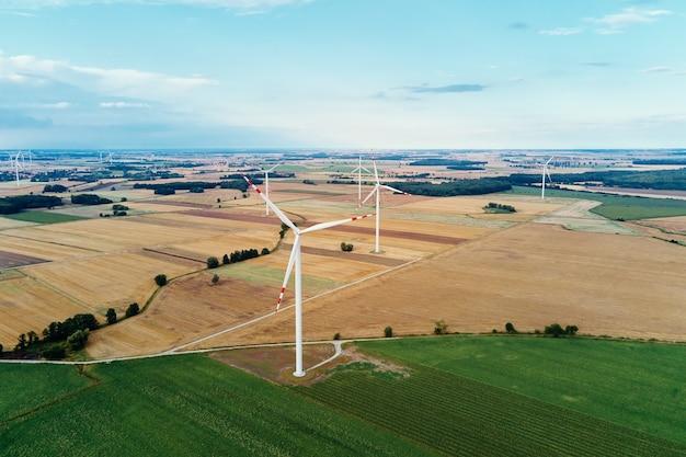 Molino de viento entre campos agrícolas generador de turbina eólica en día de verano